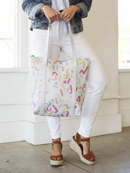 Girl wearing white jeans holding a cute tote bag in white with rainbow confetti pattern.