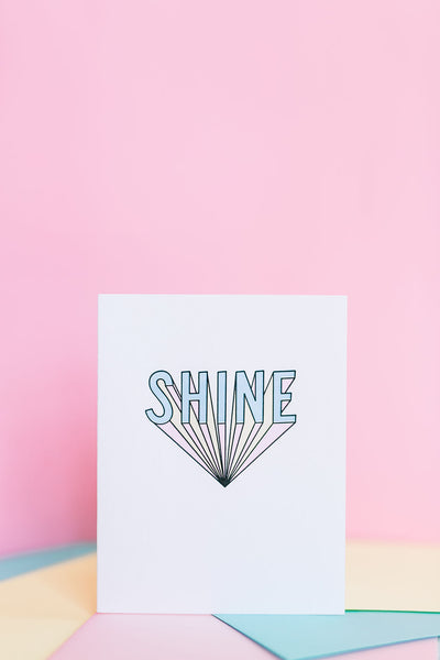 Shine card features a bold graphic of lettering with a pink background.