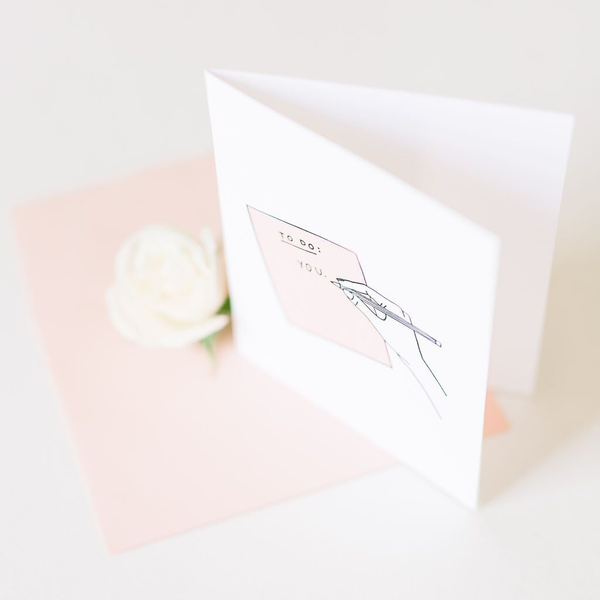 "White card with image of peach paper and a hand with a pencil. The paper says ""To Do: You"""