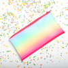 Cute rainbow pencil pouch laying on a bed of sprinkles.