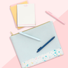 Cute stationery kit with a blue splatter pencil pouch, set of letter pressed cards, and three pastel pens on a pink background