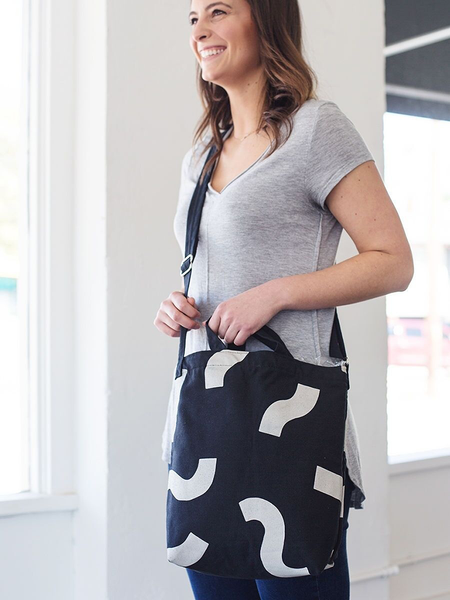 Smiling girl wearing a cute crossbody tote in black canvas with macaroni pattern.