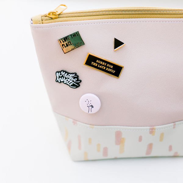 A pink pouch with sunshine pattern sits on a white surface with 5 pins pinned onto the left side of the pouch.