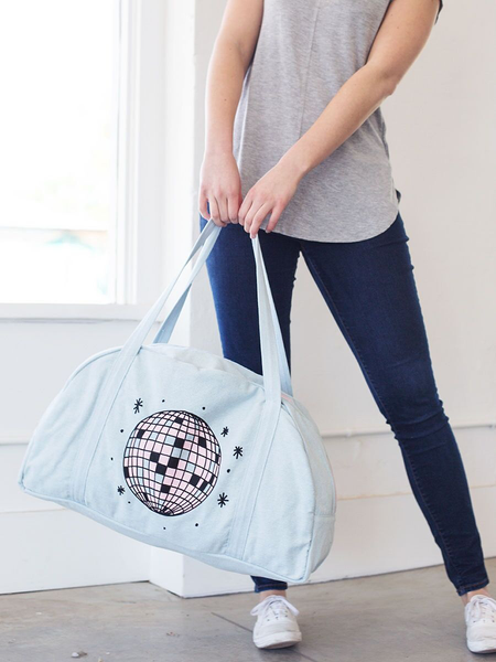 Girl in jeans swinging a cute travel bag in light denim with pink disco ball design.