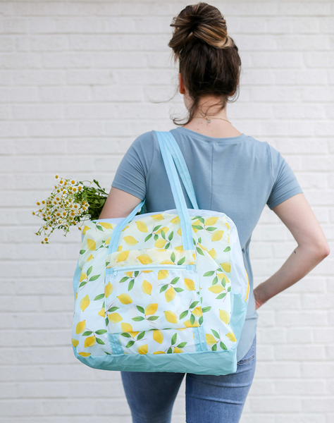 a girl holding a ripstop bag with blue straps and yellow lemons and flowers