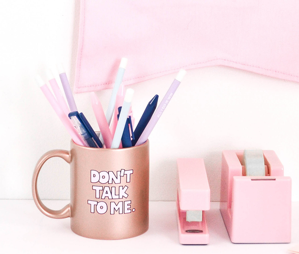 Funny coffee mug in rose gold with Don't Talk To Me written in light pink letters with black outlines next to a blush pink stapler and tape dispenser