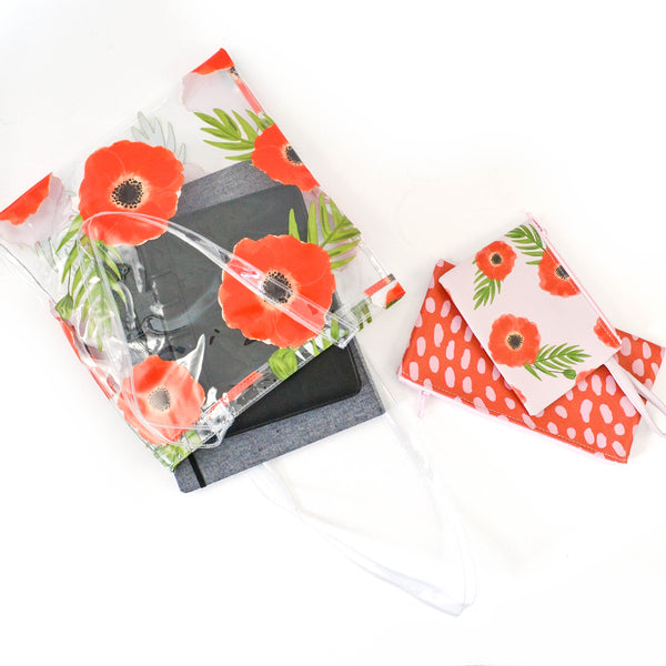 A clear vinyl bag with a red poppy pattern lays on a white surface with a small iPad visible through the bag, with two small pouches sitting beside it.