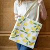 A woman holding a vegan leather tote bag printed with a pastel gradient background and lemons.