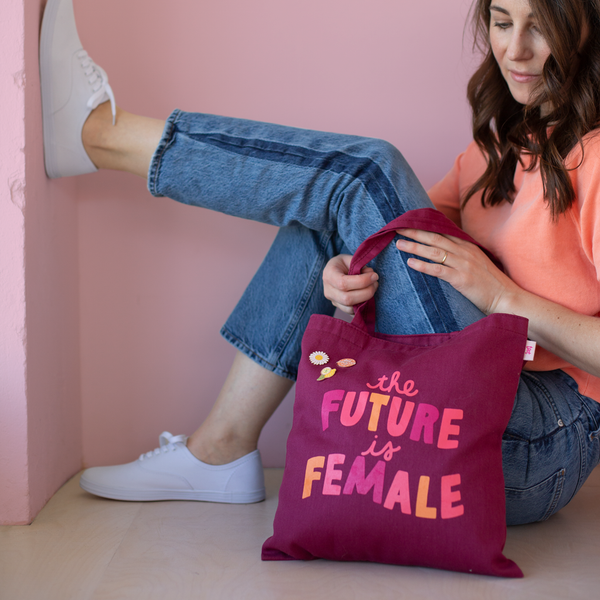 girl sitting with sangria bag with saying the future is female with enamel pins of smiley daisy flower, lemon and circle of deep breathes in