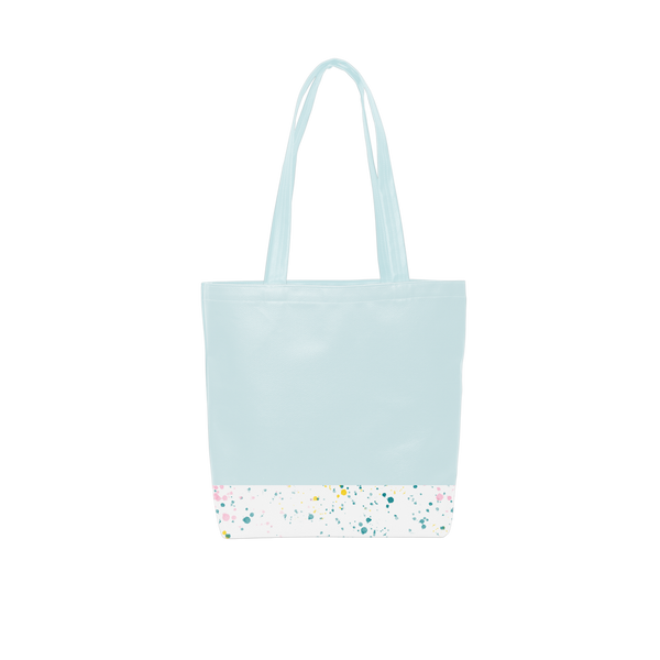 A cute tote bag with long shoulder strap in a powder blue with white paint splatter detail along the bottom.
