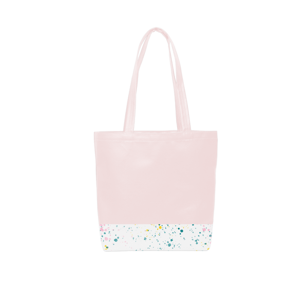 A cute tote bag with long shoulder strap in a blush pink with white paint splatter detail along the bottom.