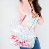 a girl holding Cute tote bag in clear vinyl with colorful pom poms.