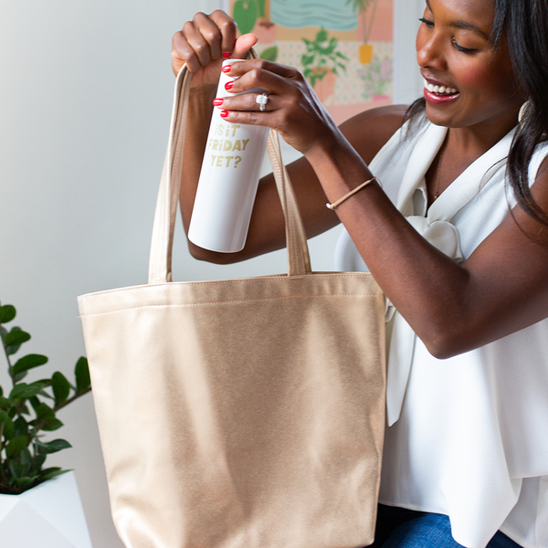 "A woman is smiling and holding a metallic gold vegan leather tote bag. She is placing a white stainless steel tumbler into the bag that says ""Is it Friday yet?"""