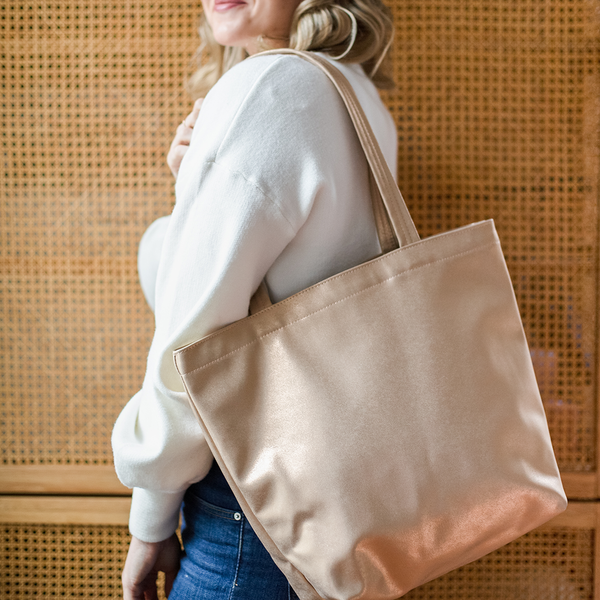 A woman has a metallic gold vegan leather tote bag on her shoulder