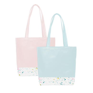 Two cute tote bags; One blue and one pink, with a long shoulder strap and white paint splatter detail along the bottom.