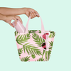 Girl's hand pulling a pink coffee tumbler out of a cute handbag with fern pattern and pink heart sunglasses hanging off the side..