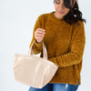 A woman holding a small metallic gold vegan leather tote bag on one arm with her hand in the bag.