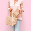 Woman in jeans and pink shirt stands holding a gold metallic open purse in one hand, and holding another small gold metallic pouch in the other.
