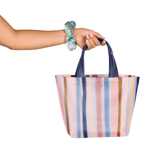 Girl with scrunchie on wrist holding a cute tote bag in purple, blue, and pink stripes pattern.