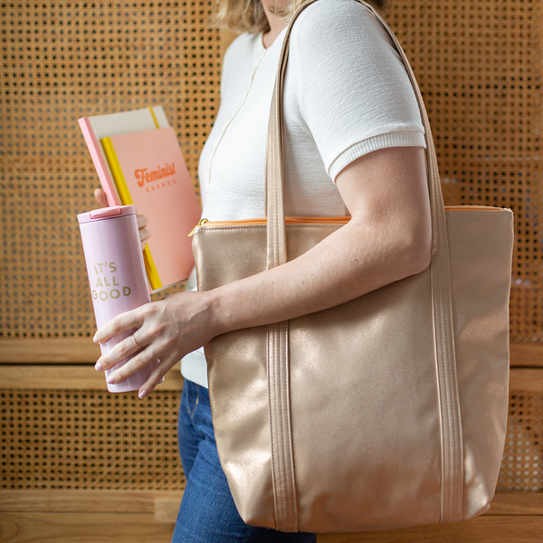 "A woman with a metallic gold vegan leather tote bag on her shoulder. She is holding a light pink stainless steel tumbler with ""It's all good"" printed on it. The other hand is holding two notebooks."