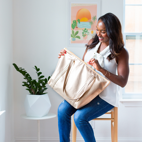 A woman holding a metallic gold vegan leather weekender tote bag. She is opening the zipper on the bag.