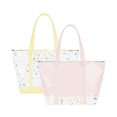 two vegan leather weekend bags. one with yellow straps and splatter all over. one pink with splatter on the bottom