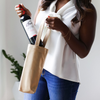 A woman holding a metallic gold vegan leather wine tote. She is placing a bottle of red wine into the tote.
