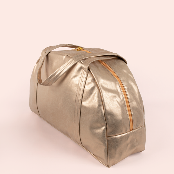 Angle view of a cute metallic gold large vegan leather zippered bag.