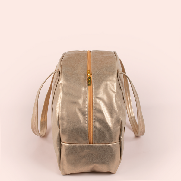Side view of a cute metallic gold large vegan leather zippered bag.