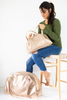 Young woman sitting on a stool with two cute metallic vegan leather zippered tote bags.