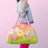 girl holding large tote with pink straps and colorful floral print