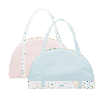Two travel tote bags, one powder blue with white paint splatter detail along the bottom and one blush pink with white paint splatter straps.