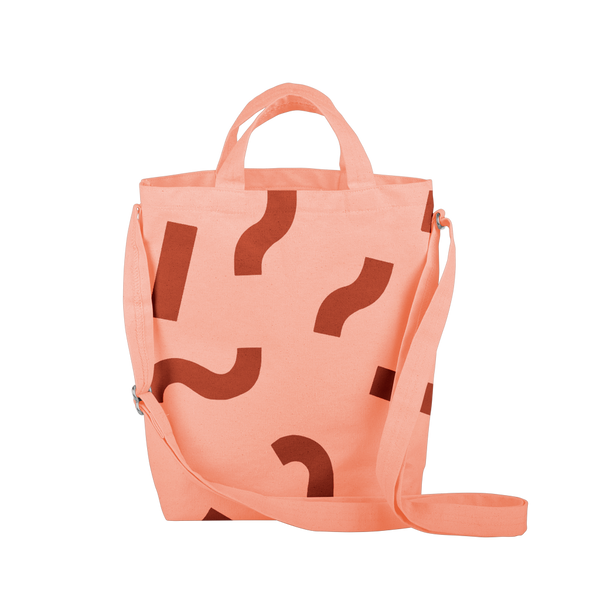 Cute tote bag in peach canvas with adjustable shoulder strap and red macaroni pattern.
