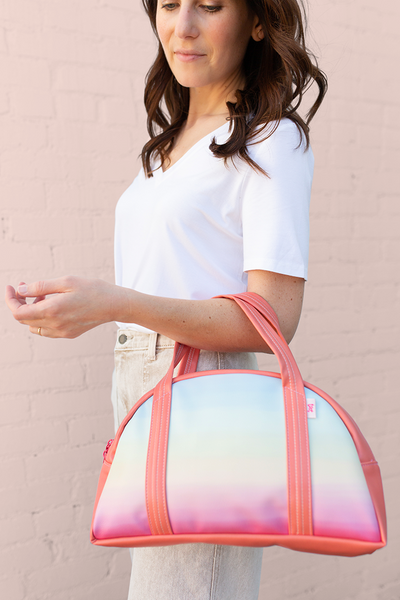 Cute tote bag in rainbow ombre with coral hand straps held by girl