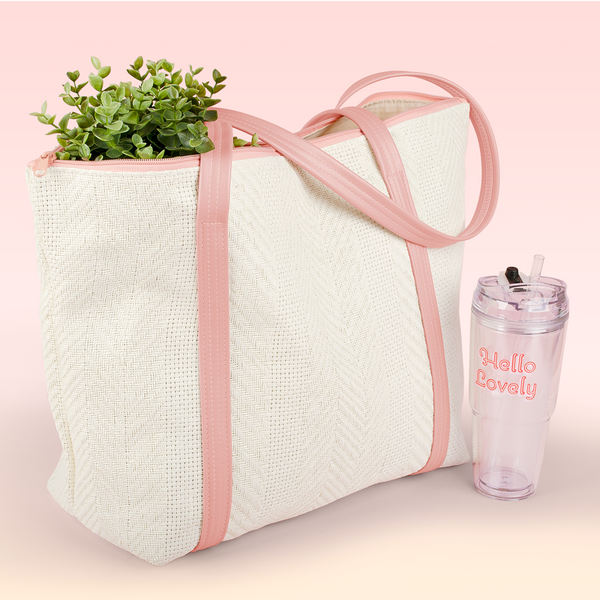 Cute straw beach tote called the Weekender with peach vegan leather straps and a plant coming out and a tumbler.