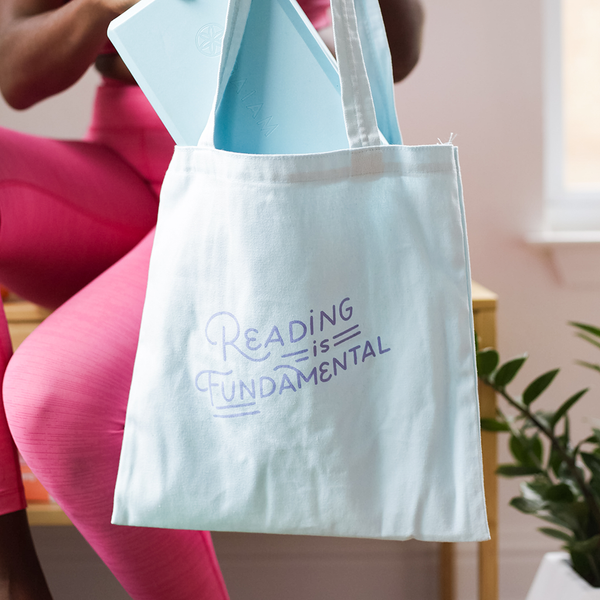 a girl holding a blue bag that says reading is fundamental