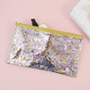 Large pencil pouch in clear vinyl with confetti glitter and a gold zipper.