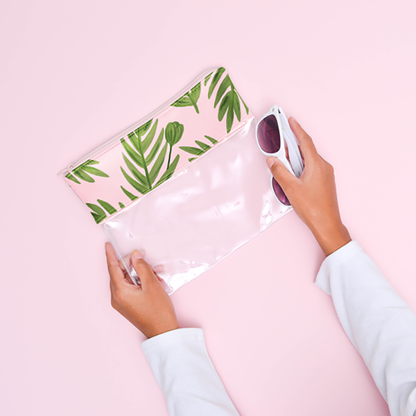 Woman holding a vegan leather and clear vinyl zippered pouch. The vegan leather is printed in pink with greenery all over. One of the woman's hands is holding onto white sunglasses.