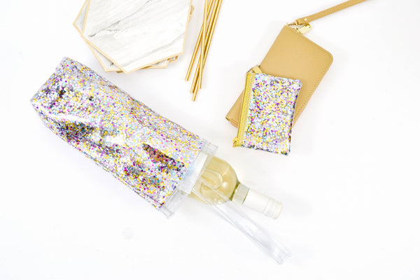 Glitter vinyl wine tote bag with white wine bottle spilling out and a confetti coin purse key ring.