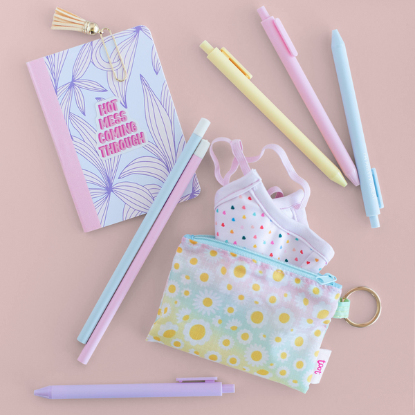 A small ombre pouch with white daisies all over and a facemask with hearts on it next to a mini notebook, pencils, and pens