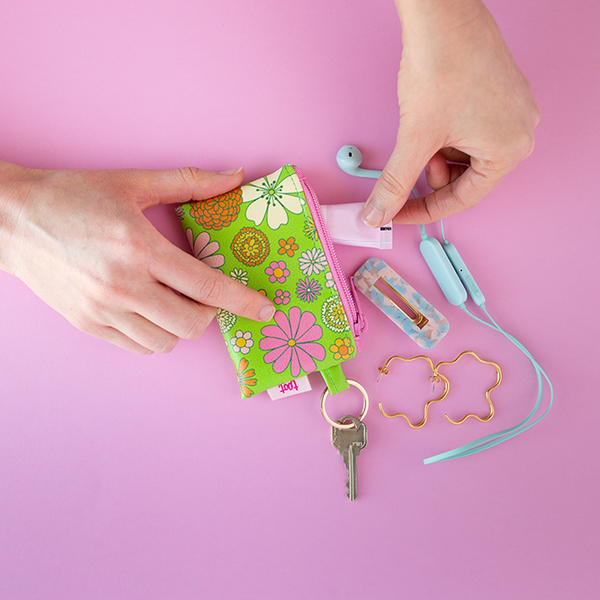 Groovy Greens Penny Key Ring is a coin purse key ring with green background with floral print on top and a pink zipper with ear buds, hands reaching in for barrette and earrings coming out of it