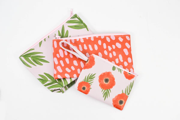 Three small pouches lay on a white surface the top one a small wristlet with a light pink background, red poppies and greenery.