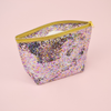 Large cosmetics bag in clear vinyl with glitter confetti lining, a gusseted bottom and gold zippered top closure.