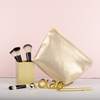 A cute makeup bag sits with a gold makeup brush holder and ciao sculpture.