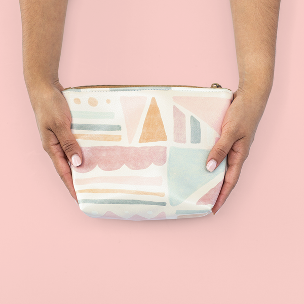 Two hands holding a cute cosmetics bag with a muted geometric print.