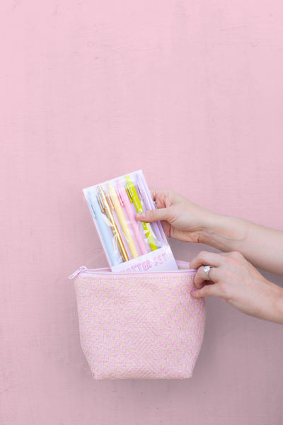 A woman's hands pulling a pack of pens from a pink straw cosmetics pouch.