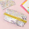 A dual layered clear vinyl confetti dopp kit with a metallic gold zipper halfway zipped. A confetti pouch is in the top left corner and notebooks are seen to the right side.