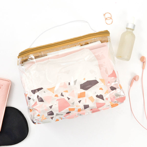 A cute toiletries bag in a terrazzo pattern surrounded by toiletries.