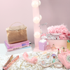 Sparkly vanity with confetti, a straightener, pink retro phone, and large toiletries bag in metallic gold.