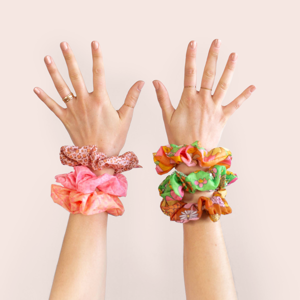 girl with both hands up in air with three rip stop scrunchies on each wrist, left with animal print and right with floral print